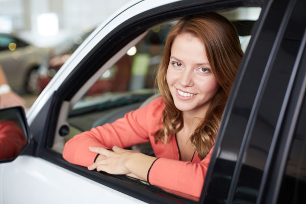Woman smiling leaning out of car window